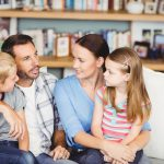 Close-up of family discussing on sofa in living room